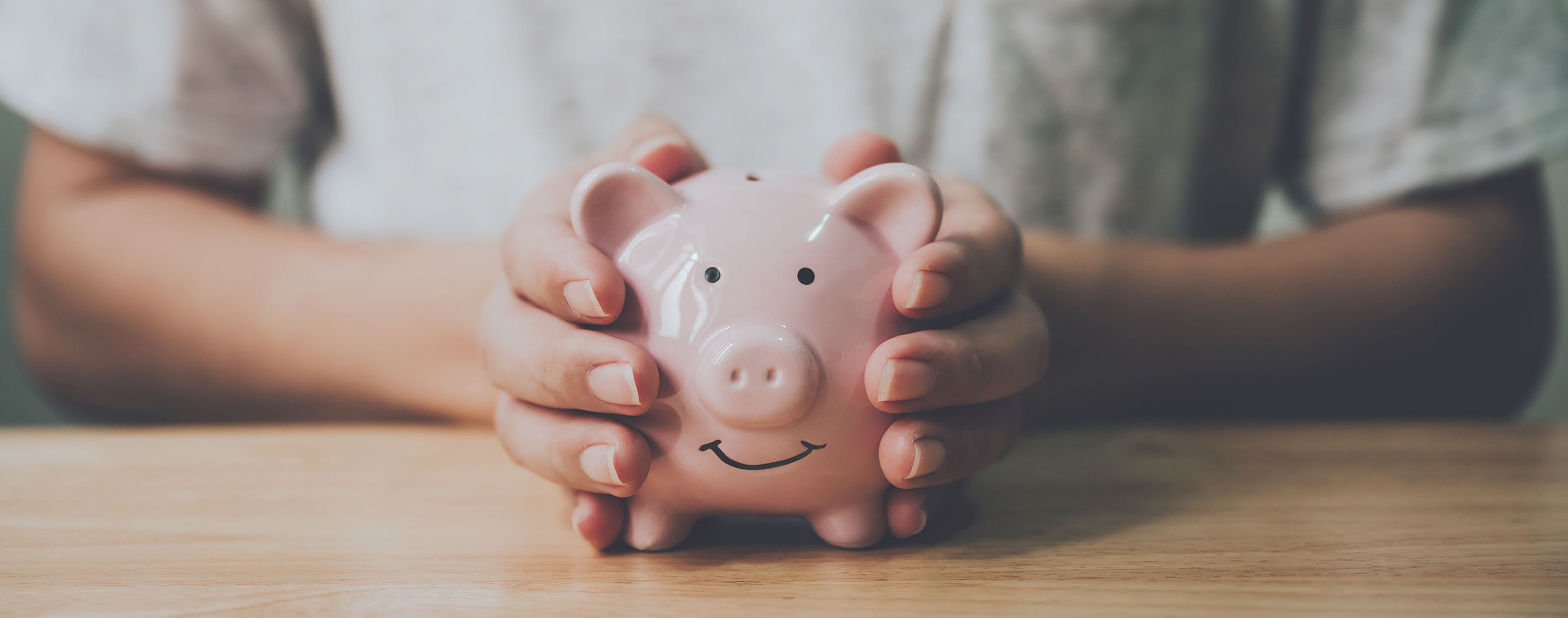 Womans hands holding a pink smiling piggy bank